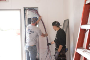 Electricians working on electrical panel
